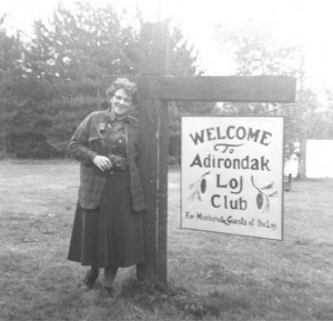 A woman standing by an old version of the Adirondak Loj sign