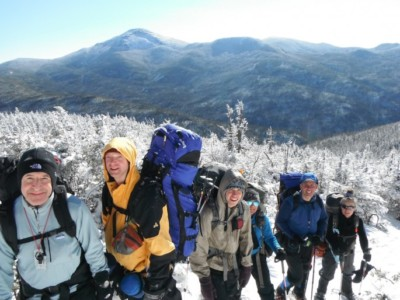 A group of winter hikers pose on a mountainside