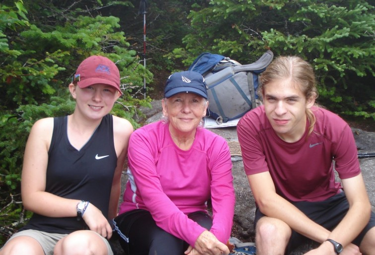 Three hikers take a break on a rock by the trail
