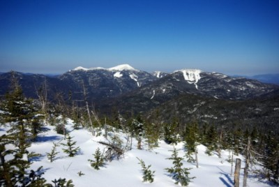View from a mountain summit in the winter showing other high peaks