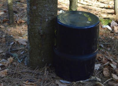 A bear canister leaning on a tree