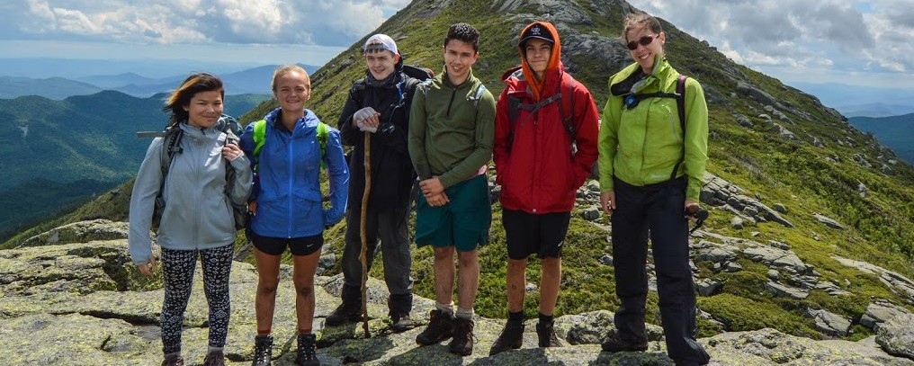 A group of five teens pose with their guide close to the summit of Mount Haystack.