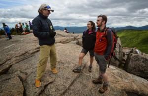 A summit steward speaks to hikers on a summit