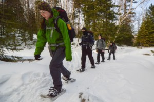 A group of people snowshoe on a trail