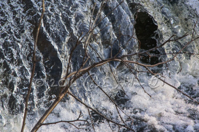 A waterfall with a branch in the foreground
