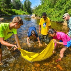 Teens strain water in a river to sample
