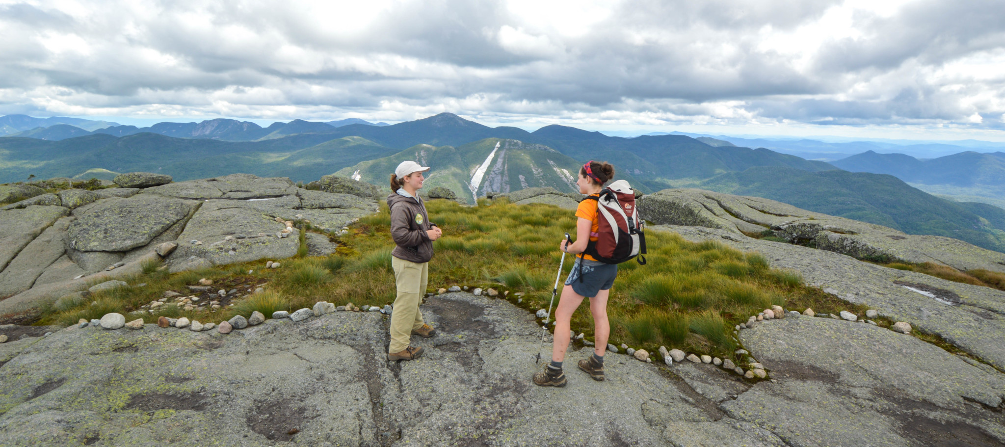 A summit steward speaks to a hiker on the summit of Algonquin