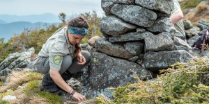 A summit steward collects rocks to build a cairn