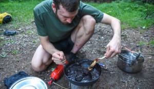 A hiker cooks on a camp stove