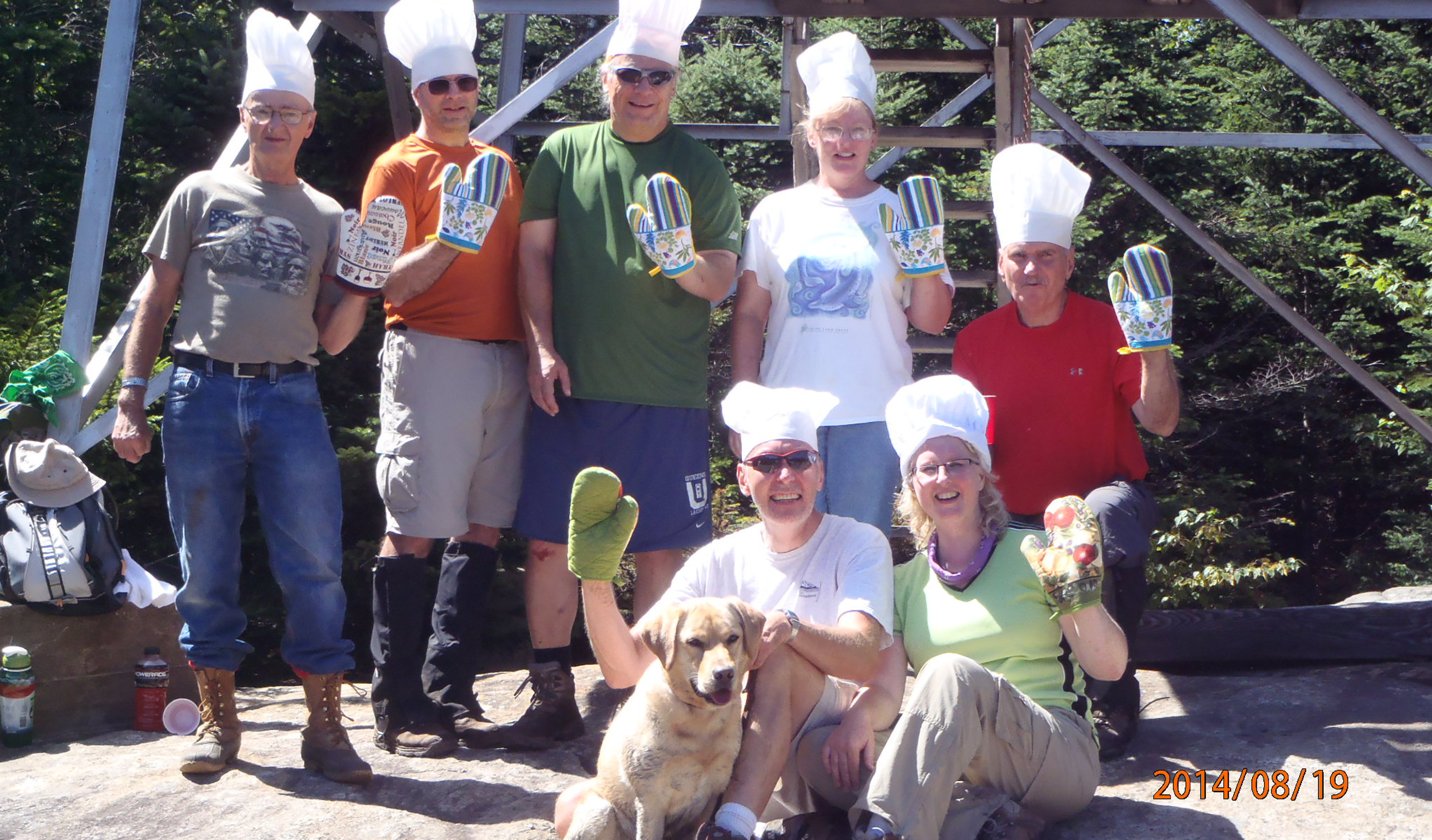 Silly group of hikers wearing chef hats and oven mitts in front of Fire Tower.