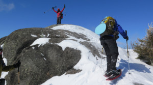 Two snowshoers celebrate on the summit