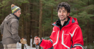 A man smiles while snowshoeing