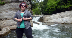 A hiker poses in front of a waterfall