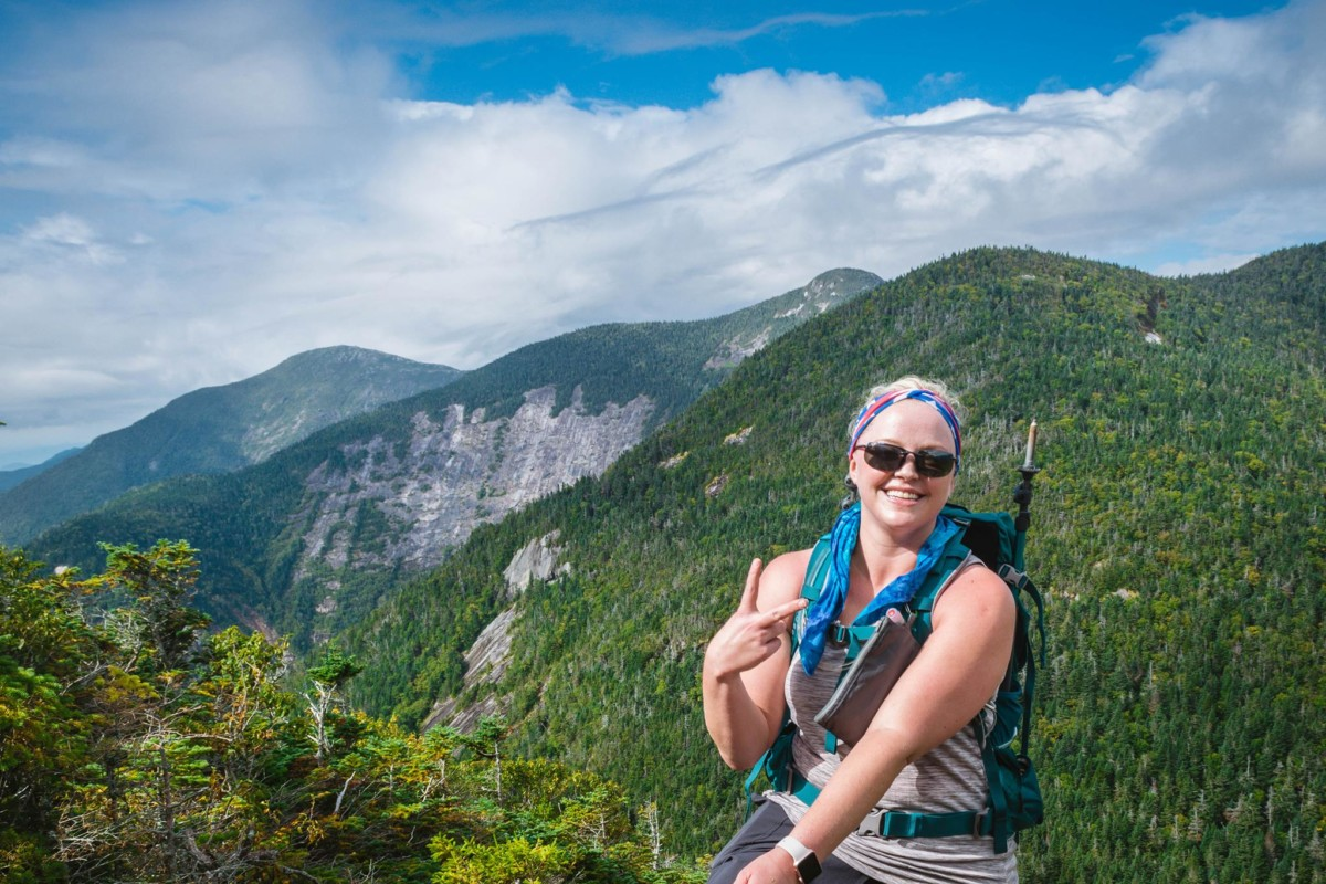 A hiker smiles for the camera while climbing Gothics