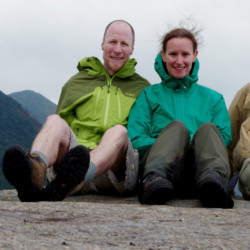Three hikers take a break under cloudy skies on the Great Range.