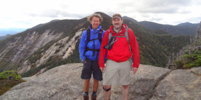Two male hikers smile for a photo on the Great Range.