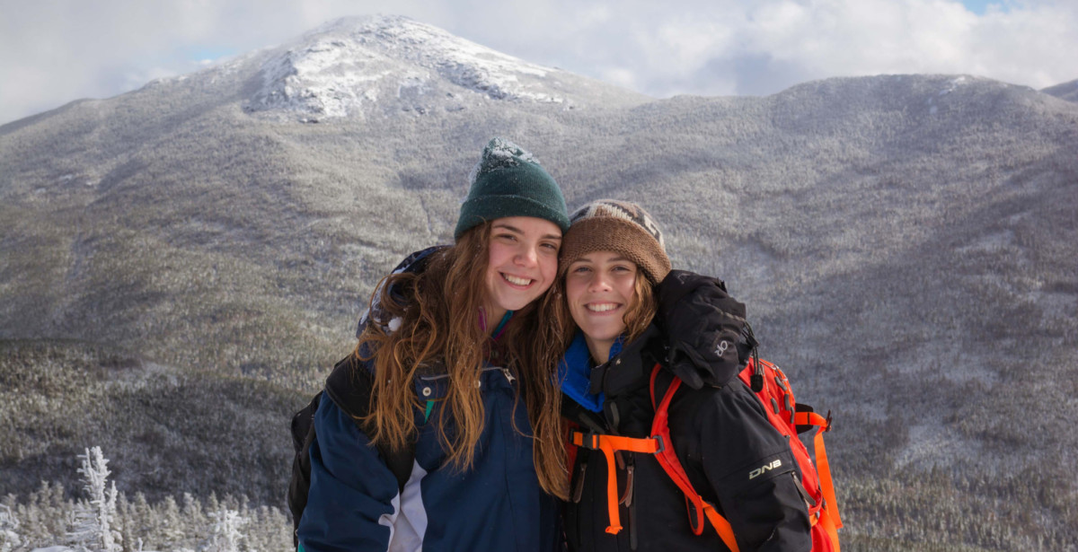 Two female hikers pose for a photo with Mount Marcy in the background.