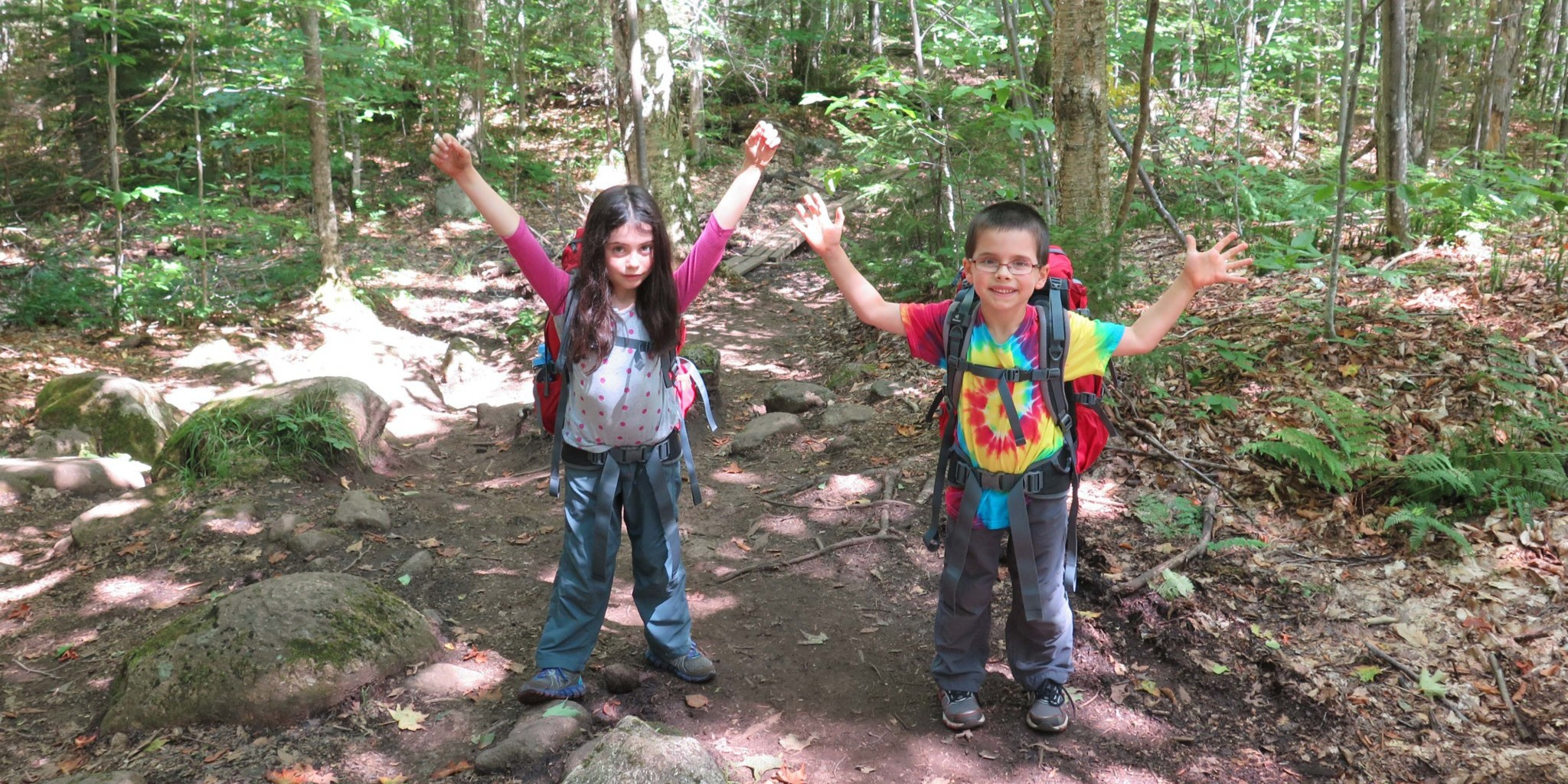 Two kids excited to be on the trail hiking.