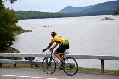 An ididaride participant cycles past a lake view