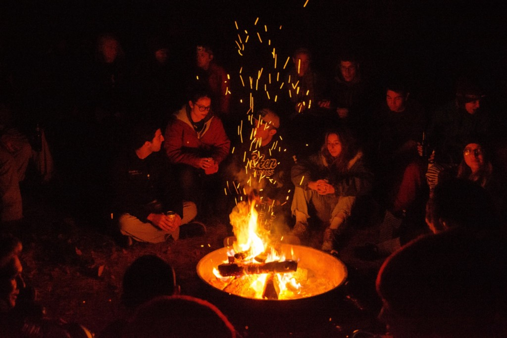 A group of people sit around a fire at night