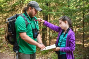 A child uses map and compass skills with the help of a naturalist in the woods.