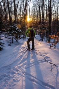 A skier watching sunset from the trail in winter