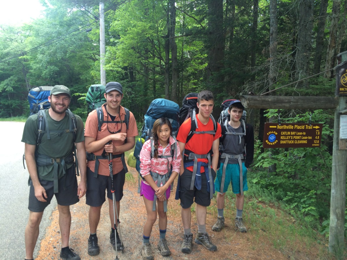 A group of teens with an instructor standing next to a trail sign with backpacks