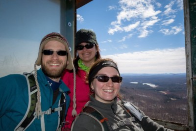 Three hikers smiling in the cab of a fire tower