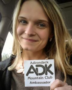 A woman holding an ADK Ambassador badge