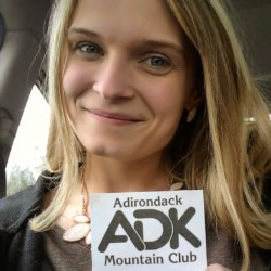 A woman holding an ADK Ambassador badge