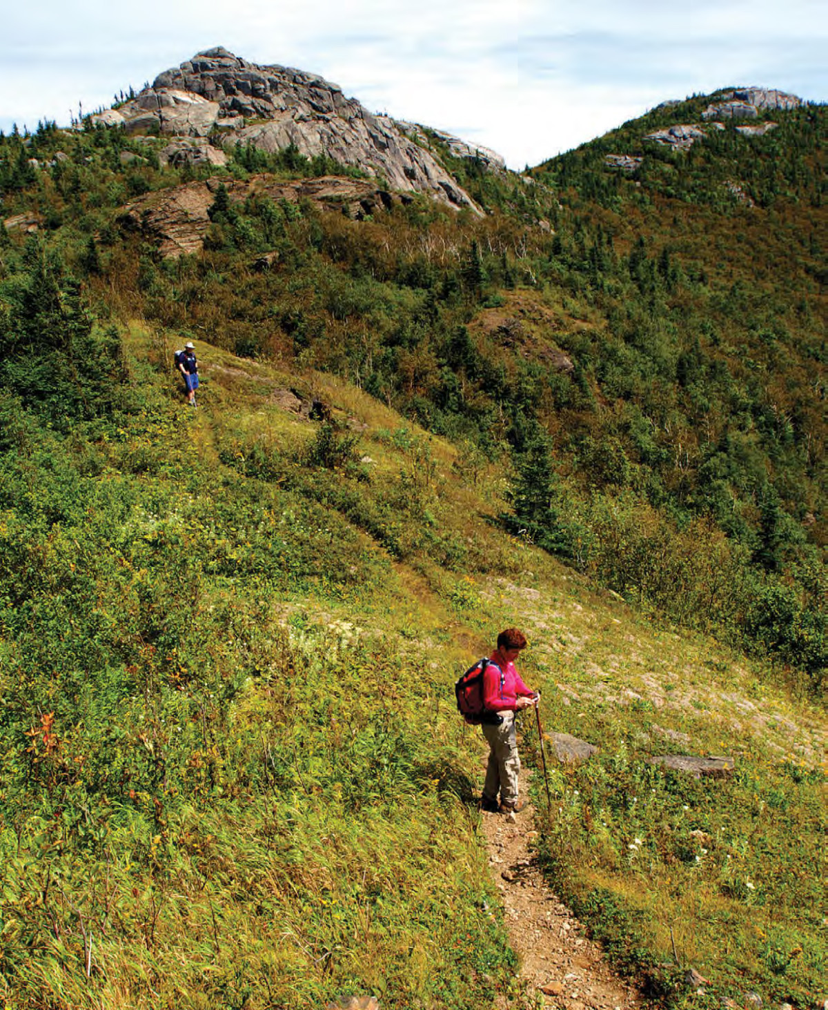 A hiker stands below a rocky summit on an open trail