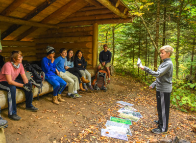 A student gives a presentation at a leanto to a group