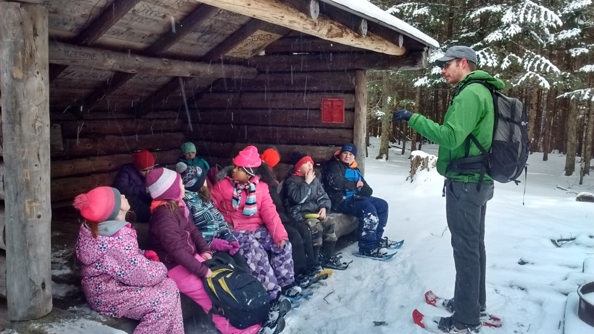 Seth Jones speaks with students in a lean-to