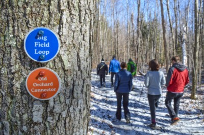 Hikers walking past trail markers in winter
