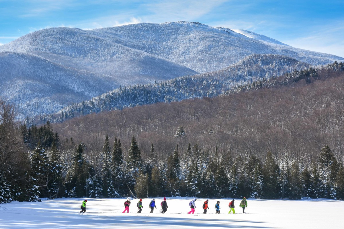 A line of school children snowshoe on Heart Lake with the MacIntyre range visible in the background