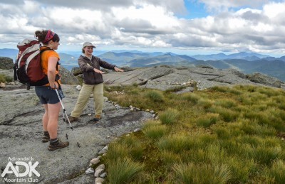 A summit steward points towards alpine vegetation while speaking with a hiker