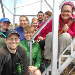 A group smiling on the lower steps of a fire tower