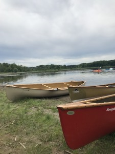 Three canoes in a row by a lake