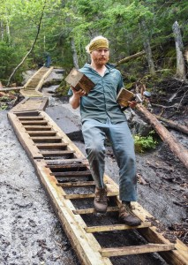 Trail crew member Peter carrying wood down a staircase