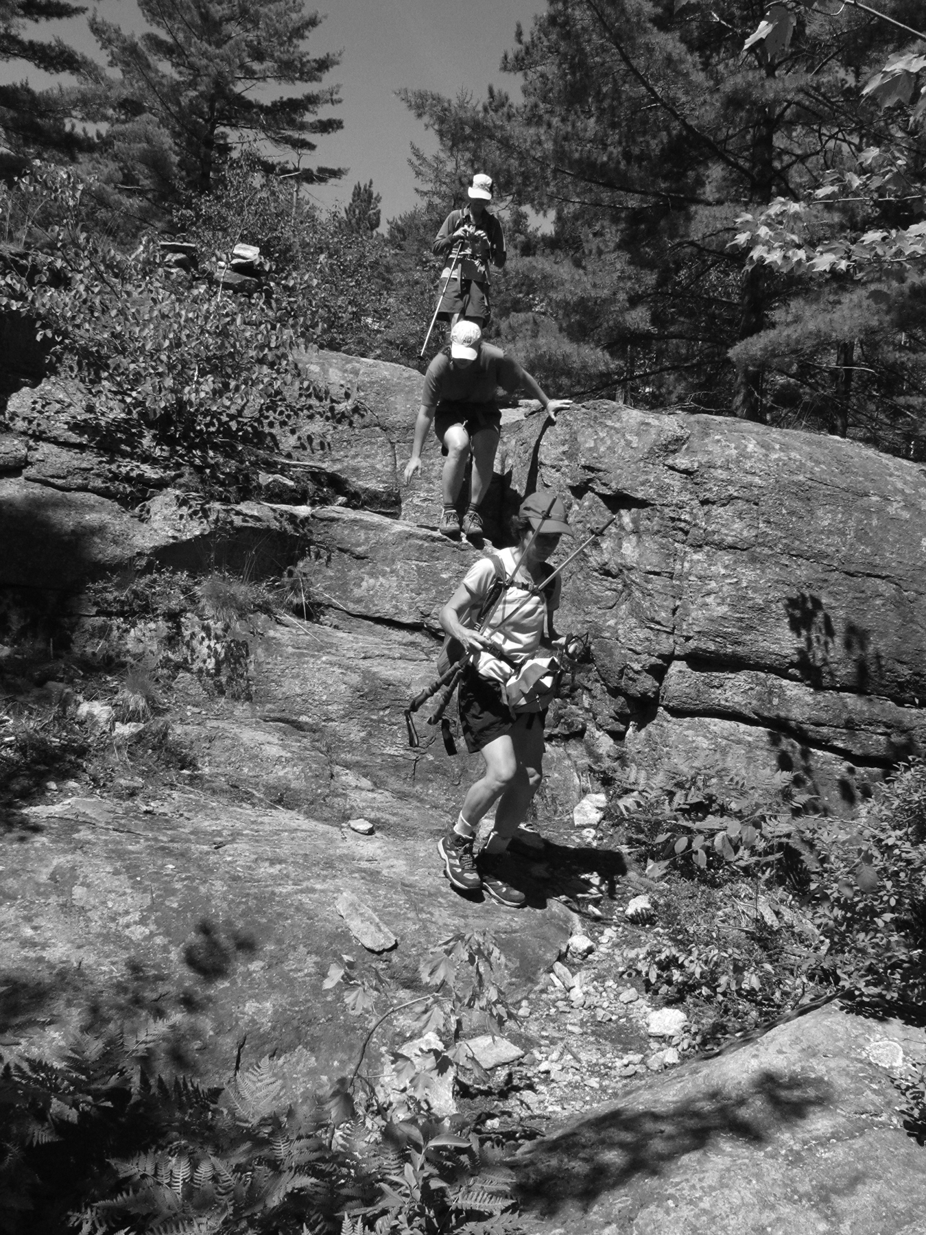 Hikers descending a steep rock section of trail