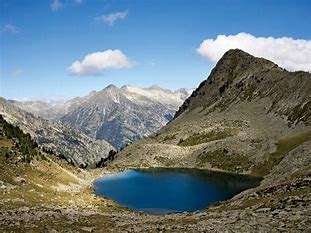 View of Spanish Pyrenees mountains and small blue lake.