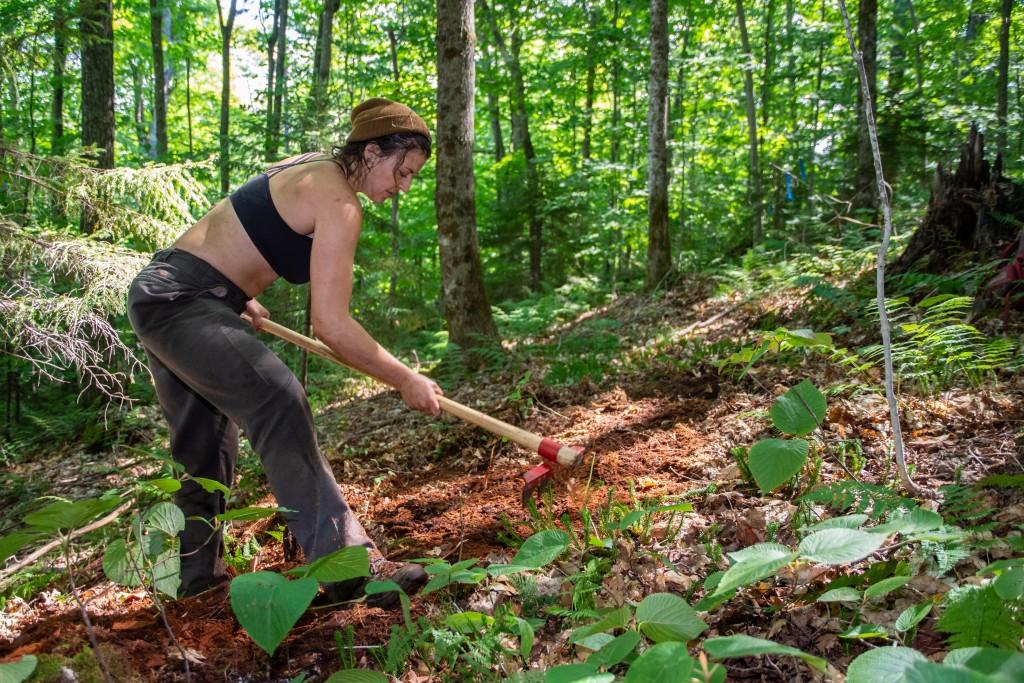 A trail crew member grubs a new trail
