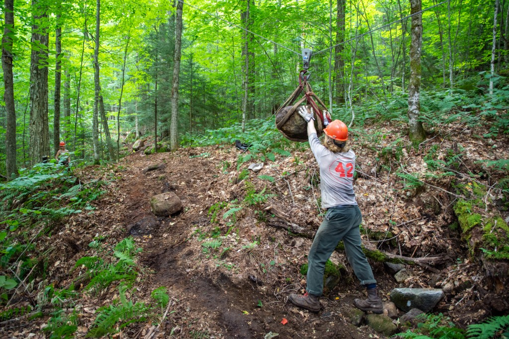 Trail crew members use a high line to move rocks