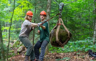 Two trail crew members winch a boulder into place