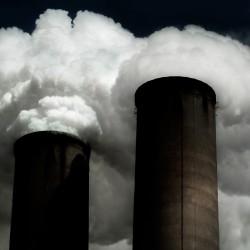 Ominous smokestacks spew clouds of smoke and vapor into a blackened sky