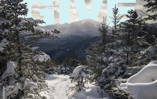 A winter mountain scene with the word GIVE in blue rising over the mountain