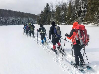 Snowshoers walking across a frozen lake