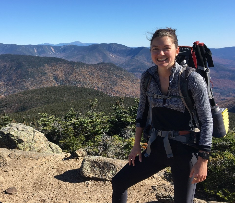 A woman smiles on the summit of a mountain