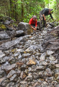 Trail crew members work on rock packing a new turnpike