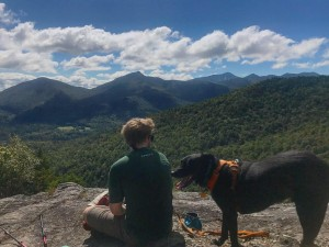 A hiker sits on the summit with a black lab
